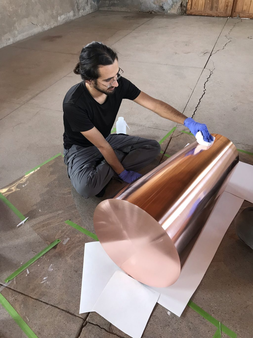 Conservation intern Christopher Gonzales cleans Horn sculpture